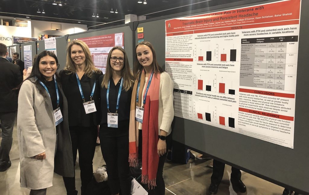 Four students smiling with arms around each other's shoulders in front of their research poster