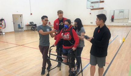 Students training with a person in walker